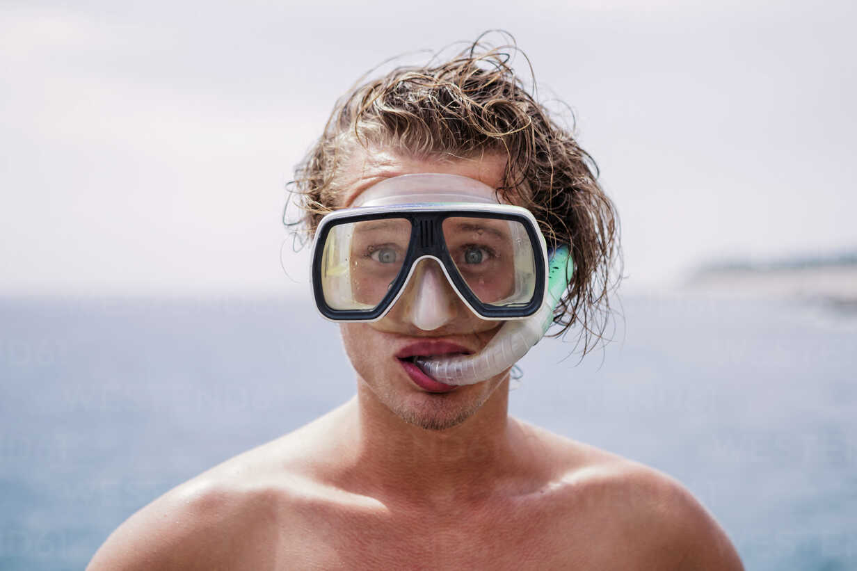 Portrait of young man with diving goggles and snorkel pulling funny faces - WVF00779 - Valentin Weinhäupl/Westend61