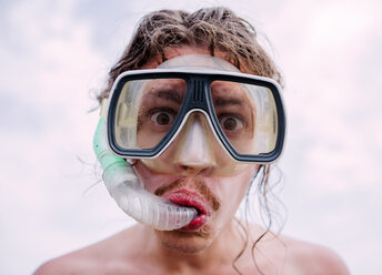 Portrait of young man with diving goggles and snorkel pulling funny faces - WVF00782