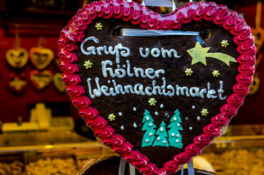 Germany, Cologne, Gingerbread heart at Christmas market stall - MHF00408