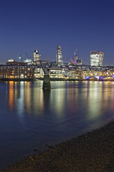 UK, London, skyline with office towers and Millenium Bridge at night - GFF00957