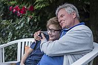 Grandfather hugging grandson on garden bench - PAF01755