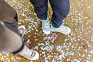 Kids standing on groung full of confetti, wearing sneakers - VABF01011
