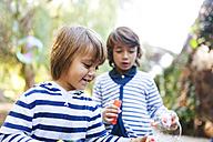 Boys blowing soap bubbles in park - VABF01017