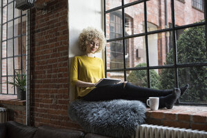 Young woman sitting on window sill, using digital tablet - RBF05531