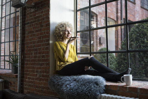 Young woman sitting on window sill, speaking into smart phone - RBF05534