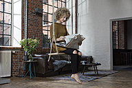 Young woman sitting on swing in living room, reading newspaper - RBF05537