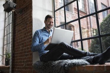 Mature man sitting on window sill, using laptop - RBF05543