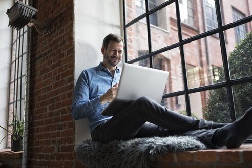 Mature man sitting on window sill, using laptop - RBF05543