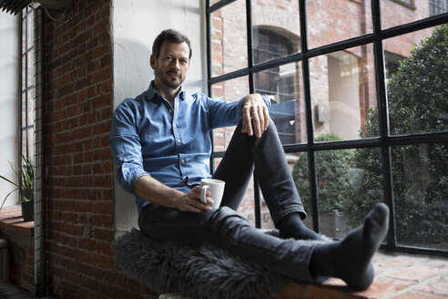 Mature man sitting on window sill, relaxing with cup of coffee - RBF05546