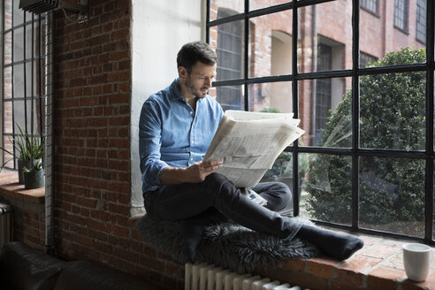 Mature man sitting on window sill, reading newspaper - RBF05549