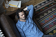 Man lying on couch, wearing head phones - RBF05555
