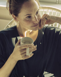Pensive young woman sitting in a chair with coffee mug - MFF03468