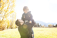Father holding happy son outdoors - VABF01027