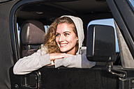 Portrait of happy young woman leaning out of car window - SIPF01331
