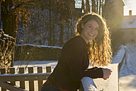 Portrait of happy young woman leaning on snow-covered railing at backlight - SARF03116