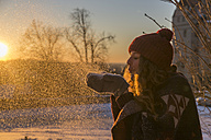 Young woman blowing snow at sunset - SARF03119