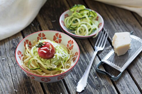 Bowl of spaghetti, zucchini spaghetti, guacamole, cherry tomato and grated parmesan - YFF00613