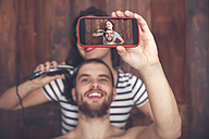 Young man taking a selfie while getting a haircut by his girlfriend with hair cutting machine - RTBF00590