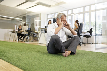 Businessman meditating in office - PESF00411
