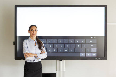 Businesswoman standing of projection of a keyboard - PESF00414