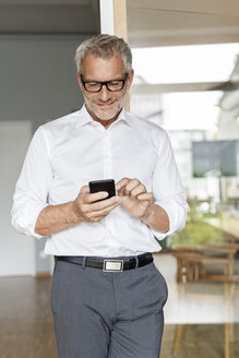 Businessman using cell phone in office - PESF00426