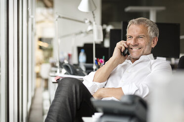 Smiling businessman on cell phone in office - PESF00438