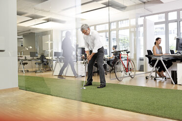 Businessman playing golf in office - PESF00456
