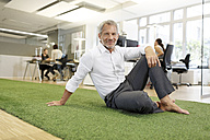 Smiling businessman sitting on carpet in office - PESF00459