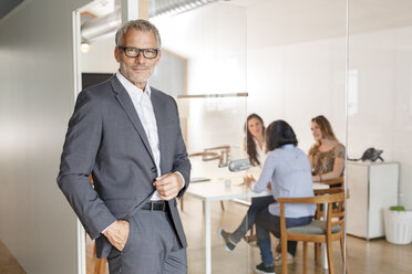 Confident businessman in office with employees in background - PESF00474