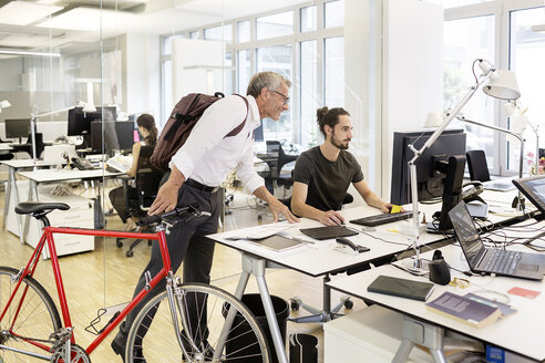Businessman with bicycle talking to colleague in modern office - PESF00498