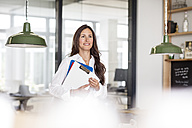 Smiling businesswoman in office holding clipboard - PESF00504