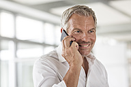 Smiling businessman on cell phone in office - PESF00507