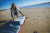 Young woman taking surfboard out of the cover on the beach - KIJF01082