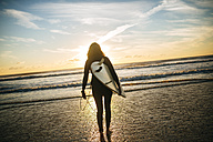 Back view of woman with surfboard on the beach by sunset - KIJF01097