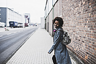 Smiling young woman with headphones and backpack on pavement - UUF09787