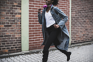 Smiling young woman with headphones and backpack running on pavement - UUF09790