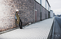 Young woman with headphones, backpack and skateboard leaning against brick wall - UUF09796