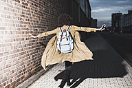 Back view of young woman with backpack running with arms outstretched - UUF09802