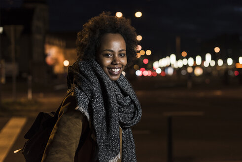 Portrait of smiling young woman at roadside by night - UUF09805