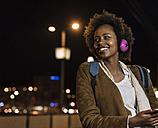 Portrait of smiling young woman with headphones waiting at the tram stop - UUF09808