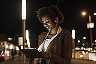 Young woman with tablet and headphones waiting at the tram stop - UUF09811