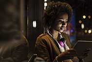 Young woman with headphones usinf tablet while waiting at the tram stop - UUF09817