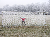 Man in soccer goal in winter - EJWF00826