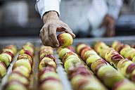 Worker taking apple from conveyor belt in factory - ZEF12418