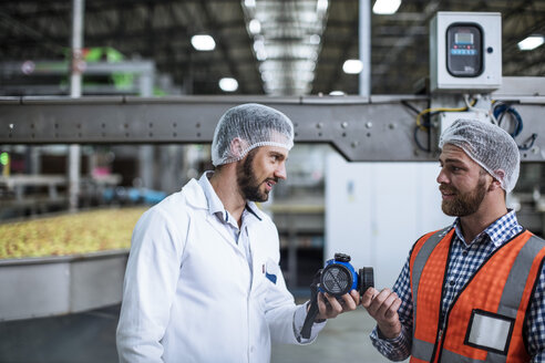 Two men talking in food processing plant - ZEF12421