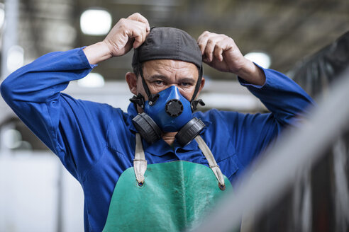 Worker putting on respirator in factory - ZEF12424