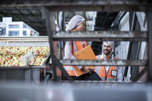 Smiling man and woman in food processing plant - ZEF12427