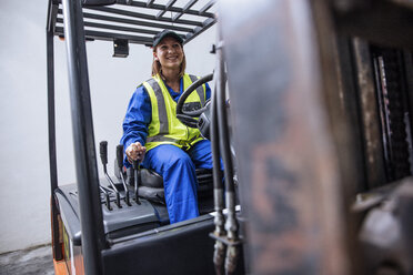 Smiling woman on forklift - ZEF12442
