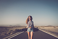 Spain, Tenerife, smiling woman with longboard standing on empty country road - SIPF01337