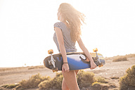 Spain, Tenerife, back view of young woman with skateboard at backlight - SIPF01340